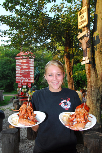 young woman holding two plates of lobsters at an outdoor eatery