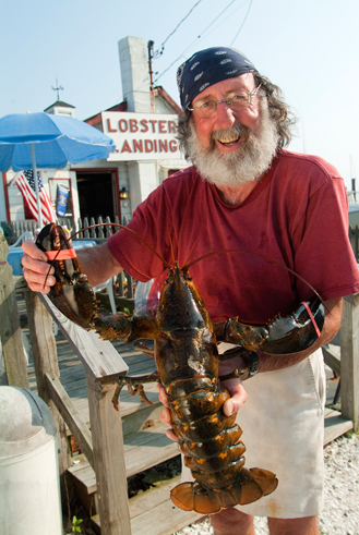 man with beard and bandana holding large lobster in front of seafood shack