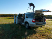 Edwina photographing in the field on top of a vehicle